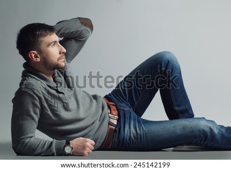 Male beauty concept. Portrait of a fashionable young man with stylish haircut wearing on sweater posing over gray background.  Hipster style. Close up. Copy-space. - stock photo