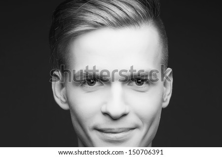 Male beauty concept. Portrait of a smiling elegant young & handsome man posing over gray background. Perfect skin & hair. Hipster style. Close up. Black and white (monochrome) studio shot - stock photo