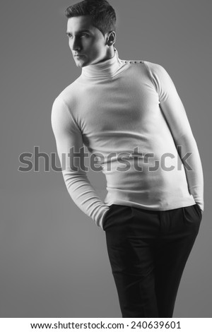 Male beauty concept. Portrait of fashionable and muscle young man in white sweater and black trousers with stylish haircut posing over grey background. Perfect hair & skin. Close up. Studio shot - stock photo