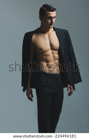 Male beauty concept. Portrait of fashionable and undressed young man in black classic suit with stylish haircut posing over gray background. Perfect hair & skin. Vogue style. Close up. Studio shot - stock photo