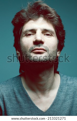 Male beauty concept. Portrait of fashionable mature handsome man in gray sweater (pullover) over dark blue background. Close up. Casual style. Studio shot - stock photo