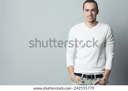 Male beauty concept. Portrait of fashionable young man with haircut wearing trendy clothes & posing over gray background. Perfect smile & skin. Casual street style. Copy-space. Studio shot - stock photo