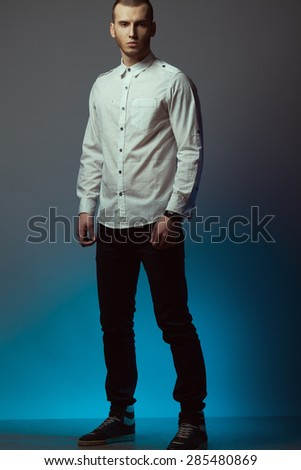 Male beauty concept. Portrait of fashionable young man with haircut wearing trendy clothing, sport footwear & posing over blue and gray background. Casual street style. Studio shot - stock photo