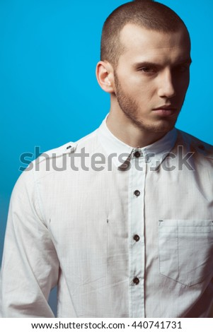 Male beauty concept. Portrait of fashionable young man with haircut wearing trendy shirt & posing over blue background. Casual street style. Close up. Studio shot - stock photo