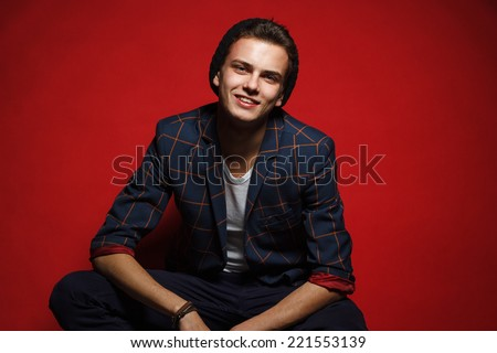 Male beauty concept. Portrait of fashionable young man with stylish haircut, posing over red background. Perfect hair & skin. Hipster style. Copy-space. Studio shot - stock photo