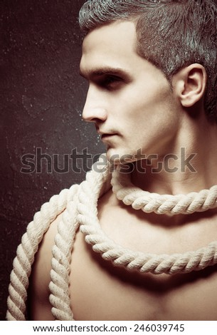 Male beauty concept. Portrait of handsome and undressed young man with stylish haircut posing over grey background. Perfect hair & skin. Close up. Studio shot - stock photo