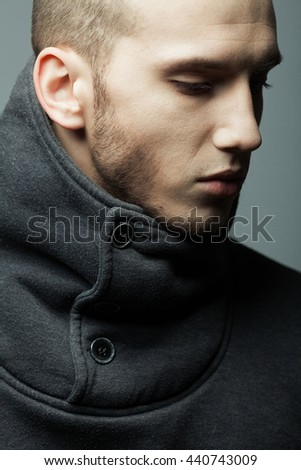 Male beauty concept. Profile portrait of brutal young man with short hair wearing gray sweatshirt with high collar and buttons posing over gray background. Modern street style. Close up. Studio shot - stock photo
