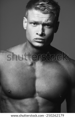 Male beauty & fitness concept. Portrait of handsome muscular male model with perfect body posing over gray background. Blond hair and healthy clean skin. Close up. Black and white studio shot - stock photo