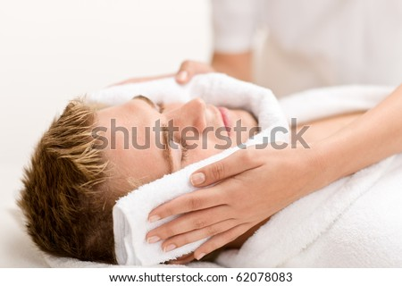 Male beauty - man at luxury spa treatment receiving facial massage - stock photo