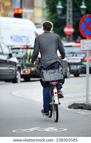 Male bicyclist on the street, with headphones - stock photo