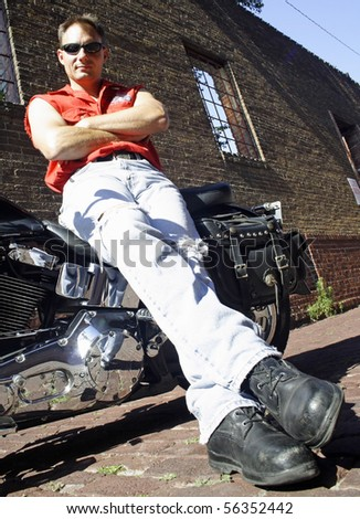 Male biker sitting on motorcycle on brick street. - stock photo
