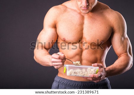 Male bodybuilder posing on a dark background. Muscular man eating healthy food - rice. Man holding a tray with rice and eat with a fork. Rice, health, muscles, food - healthy eating concept. - stock photo
