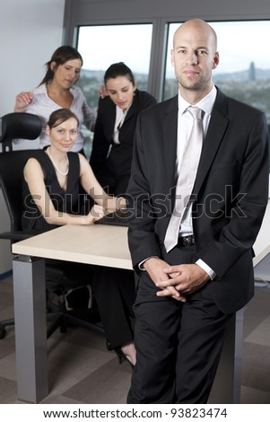 Male boss standing in front of his collegues - stock photo