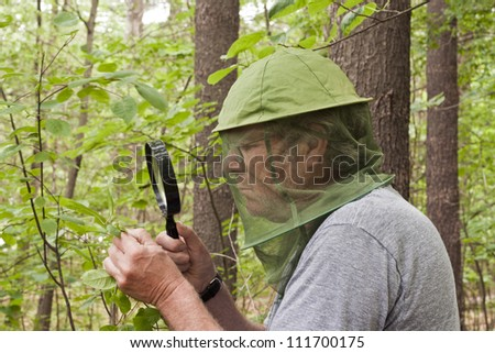 male botanist inspecting a plant with a magnifying glass - stock photo
