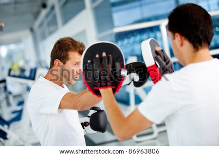 Male boxer at the gym with his trainer - stock photo