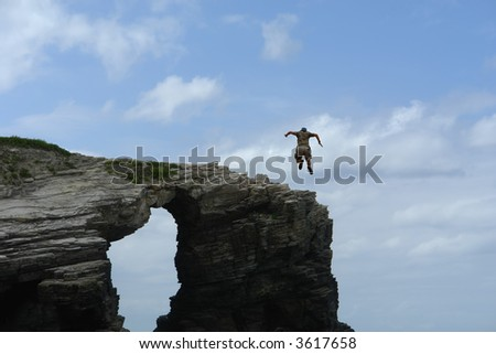 male boy jumping from a big rock