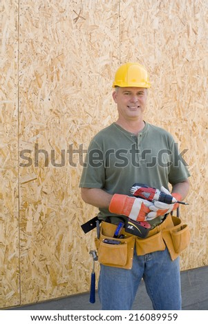 Male builder in hardhat with electric drill, smiling, portrait