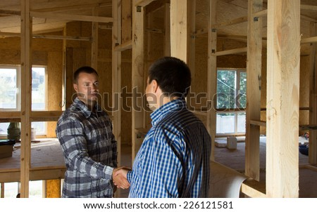 Male Building Planners Doing Handshake After the Deliberation of Proposed Designs. Emphasizing Positive Agreement. - stock photo