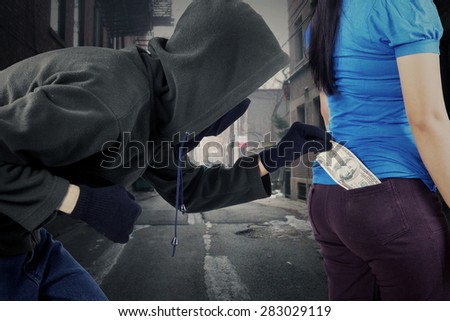 Male burglar in action to stole money while wearing black jacket, mask, and gloves - stock photo