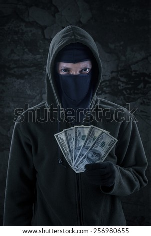 Male burglar wearing mask and hoodie, looking at the camera while holding the money stolen