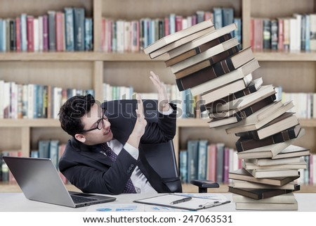 Male business college student holds falling books in the library - stock photo