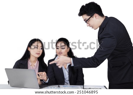 Male business leader pointing at laptop to explain a job on his subordinates, isolated on white - stock photo