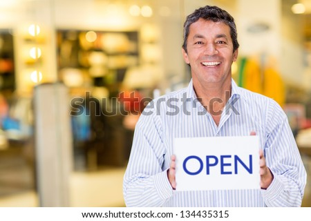 Male business owner holding an open sign and smiling - stock photo