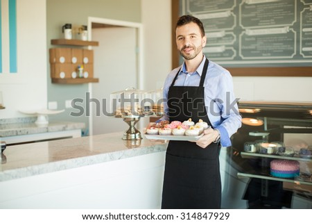 Male business owner in an apron holding a tray of cupcakes and standing in front of his bakery - stock photo