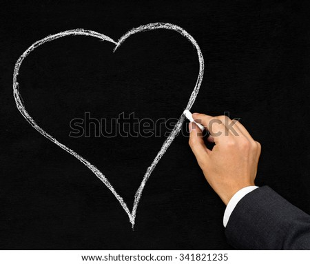 Male businessman drawing shape of a heart with chalk on blackboard background - stock photo