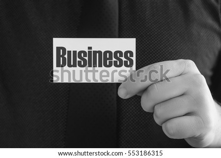 Male businessman in a shirt and tie is holding a business card with the text Business