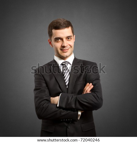 male businessman in suit with crossed hands, looking on camera - stock photo