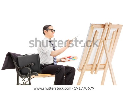 Male businessman painting on a canvas isolated on white background - stock photo