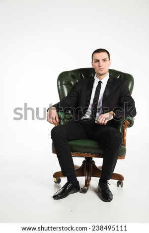 Male businessman sitting on a green leather chair on a white background.  The man exudes