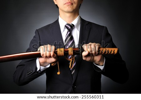 Male businessman wearing a suit to have the sword of Japanese samurai - stock photo