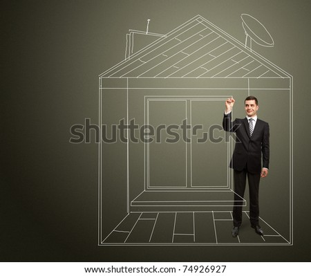 male businessman with marker in fictional house writing something on glass write board - stock photo