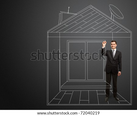 male businessman with marker in fictional house writting something on glass writeboard - stock photo