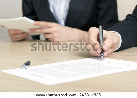 Male businessperson signs contract. Close up of female hand signing formal paper on the office table. The business counterpart on the background. - stock photo