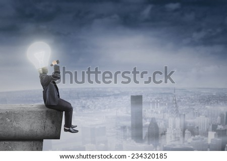 Male businessperson with lightbulb head sitting on roof and using binocular to see his vision - stock photo
