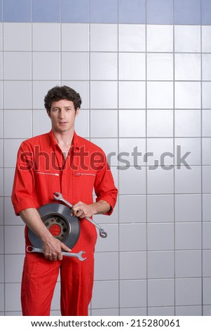 Male car mechanic, in red overalls, standing in auto repair shop near tiled wall, holding vehicle part and wrenches, smiling, portrait - stock photo