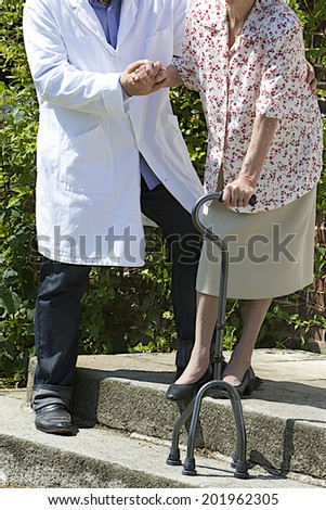 Male caregiver helping  senior patient with walking stick on  the stairs outdoors