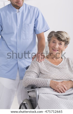 Male carer and conetent senior woman sitting on a wheelchair, light background