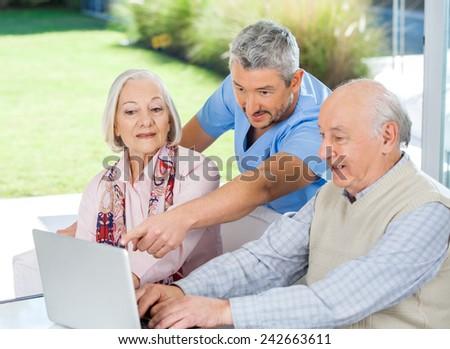 Male caretaker assisting senior couple in using laptop at nursing home porch - stock photo