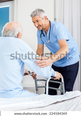 Male caretaker assisting senior man to use walking frame in bedroom at nursing home - stock photo