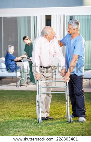 Male caretaker comforting senior man while assisting him in using Zimmer frame at nursing home lawn - stock photo