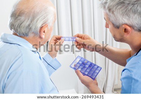 Male caretaker showing prescription medicine to senior man in bedroom at nursing home - stock photo