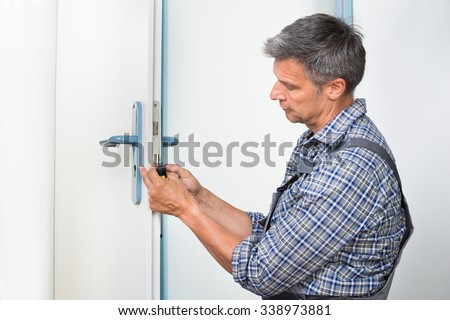 Male carpenter fixing lock in door with screwdriver at home - stock photo