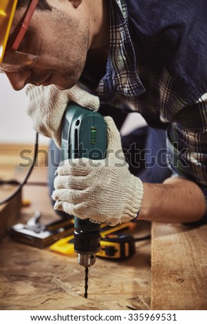 Male carpenter with drilling instrument working at home on the floor. Concept of house improvement and renovation.  - stock photo
