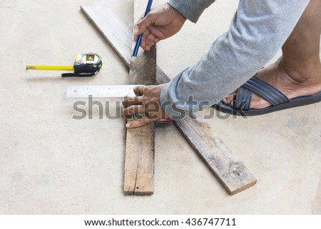 Male carpenter working with wood pencil and tape measure at work place.Background craftsman tool.Zoom in