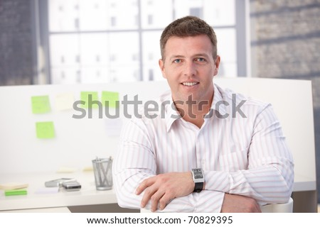 Male casual office worker smiling in office, sitting.? - stock photo