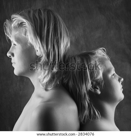 Male Caucasian adolescent and teen brothers standing back to back. - stock photo
